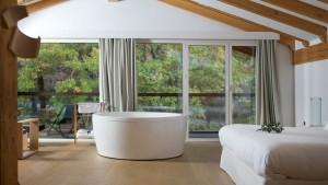 Laztana - bañera redonda junto a ventanales con vistas al bosque