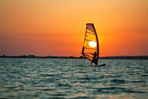 Seascape of still sea surface, man practicing wind surfing and golden sunset in sky on summer clear day. Still landscapes of travels and destination scenics