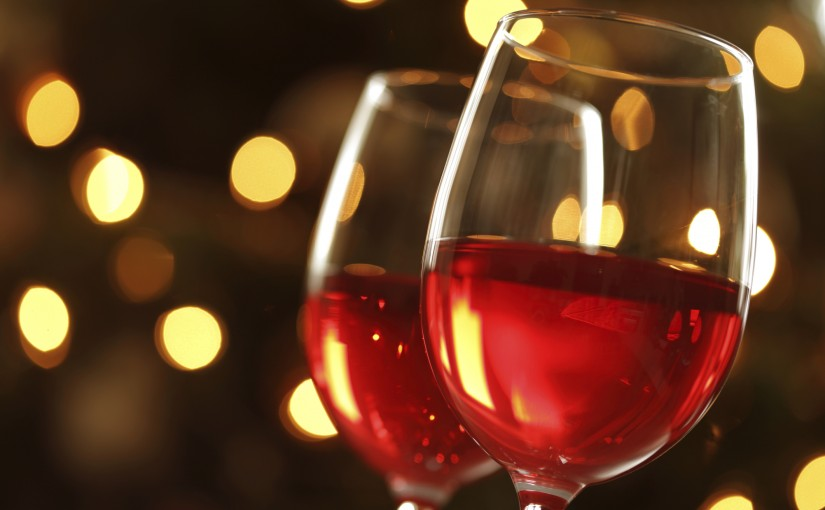 Glass of red wine against defocussed lights